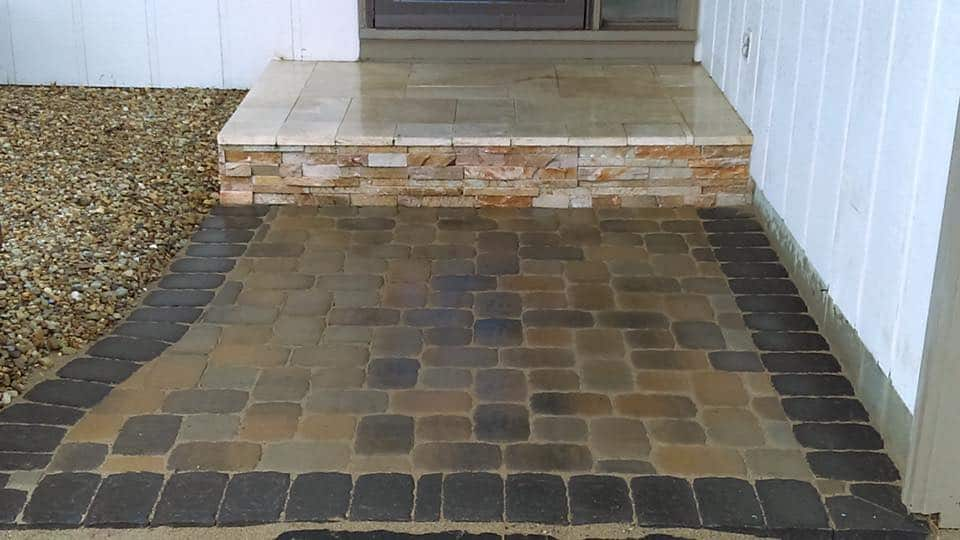 jonthan allen – paver patio – traverteen landing with a veneer facing finished with a paver patio touched with a charcoal solder course